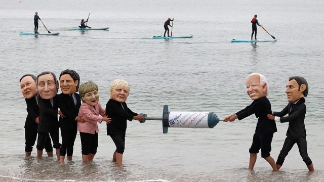 Instando a los países más ricos a que compartan las vacunas con los países más pobres, los manifestantes hacen un simulacro en la playa cercana a el encuentro del G7.
