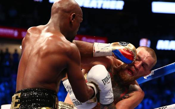 Floyd Mayweather Jr. lands a hit against Conor McGregor during a boxing match at T-Mobile Arena