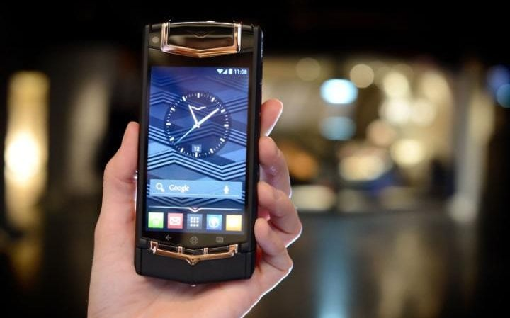 A woman holds a Black PVD Titanium Red Gold and Mixed Metals Vertu Ti smartphone