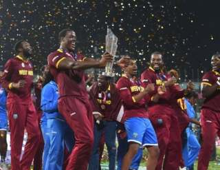 West Indies's Carlos Brathwaite (C) holds the trophy as he celebrates after winning the World T20 cricket tournament final match between England and West Indies
