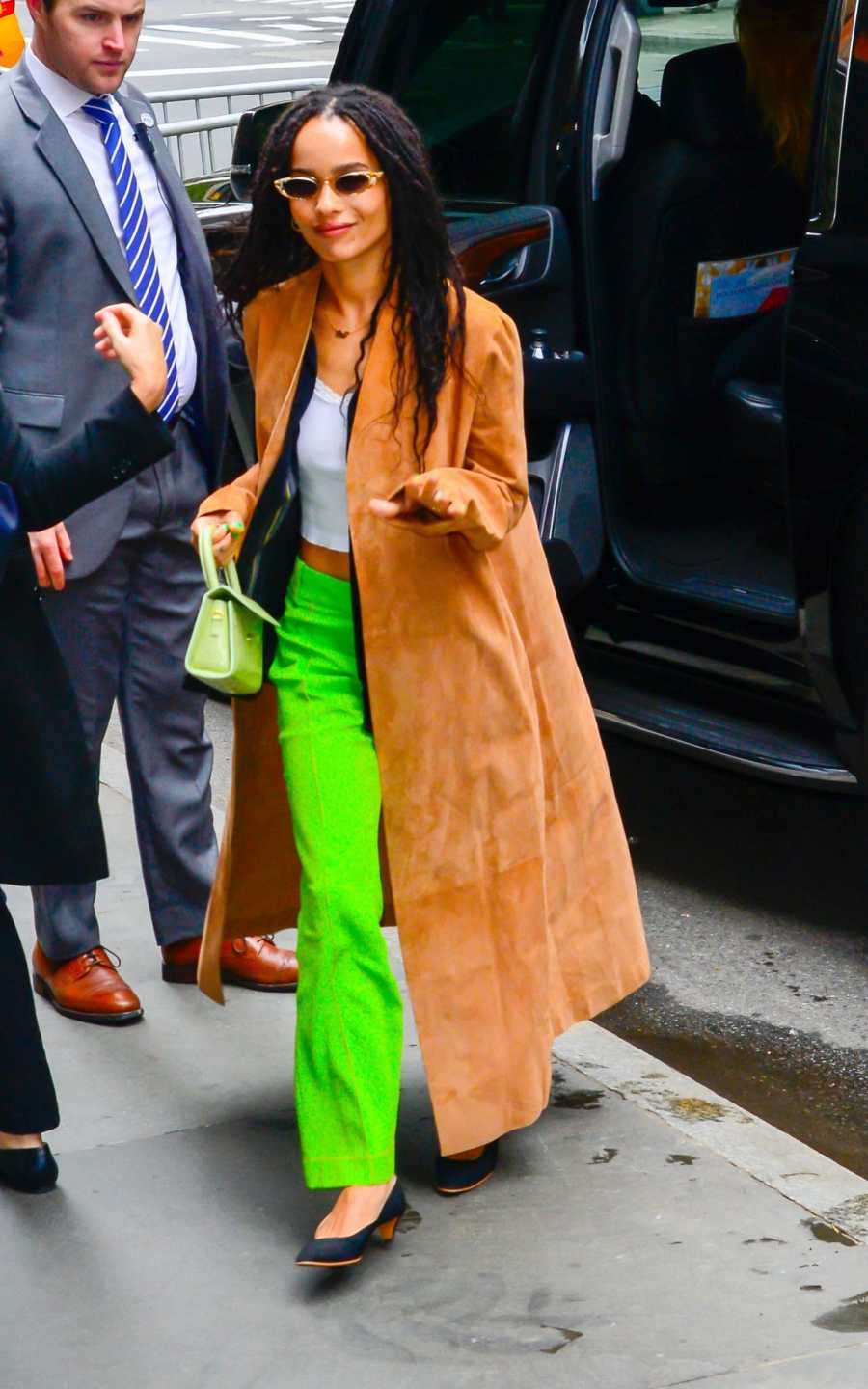 Zoe Kravitz in a brown coat and green trousers and a mini bag
