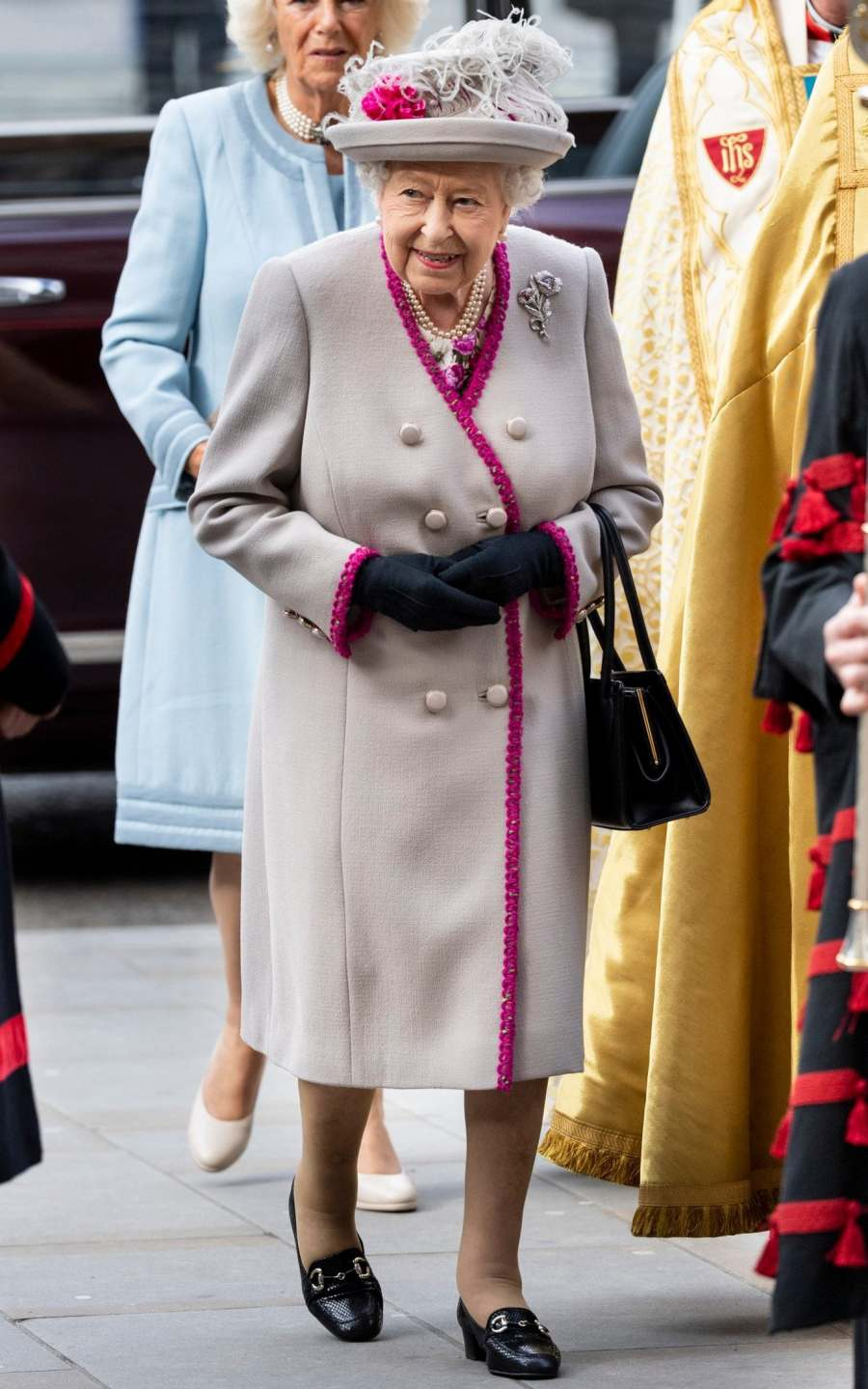 The Queen at the 750th anniversary of Westminster Abbey wearing a cream coat with a pink trim and a feather hat