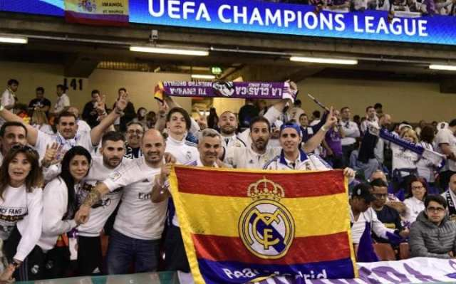 Real Madrid supporters pose for a photograph as the atmosphere builds inside the stadium