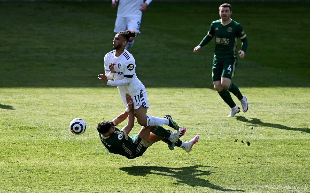 Tyler Roberts of Leeds United is tackled by George Baldock of Sheffield United during the Premier League match between Leeds United and Sheffield United at Elland Road on April 03, 2021 in Leeds, England.