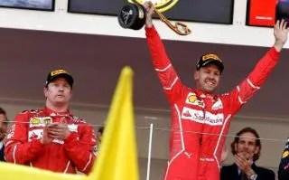 Sebastian Vettel celebrates on the podium next to second placed Ferrari's Finnish driver Kimi Raikkonen