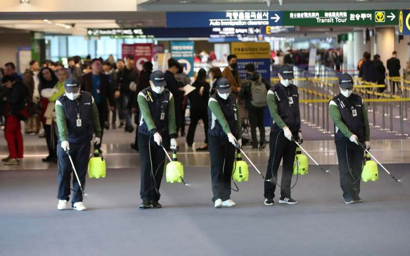 Workers spray antiseptic solution on the arrival lobby amid rising public concerns over the possible spread of a new coronavirus at Incheon International Airport in Incheon, South Korea