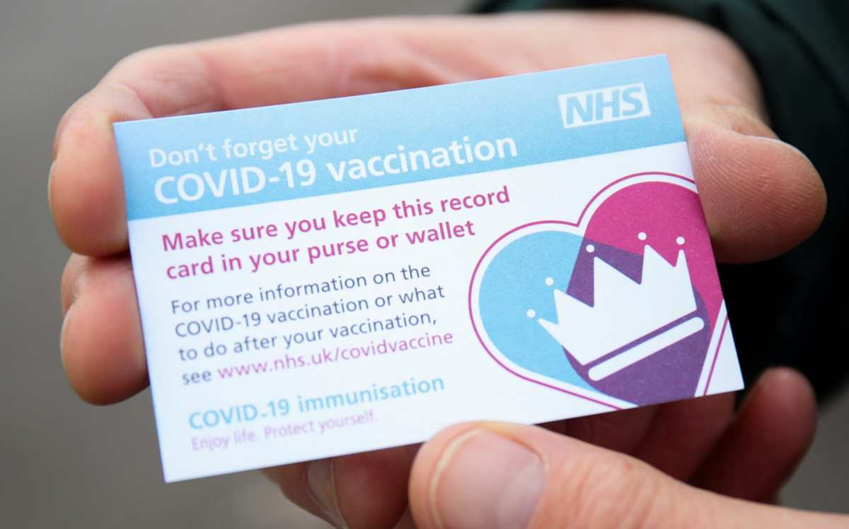 A COVID-19 vaccination record card is seen at a drive through vaccination centre