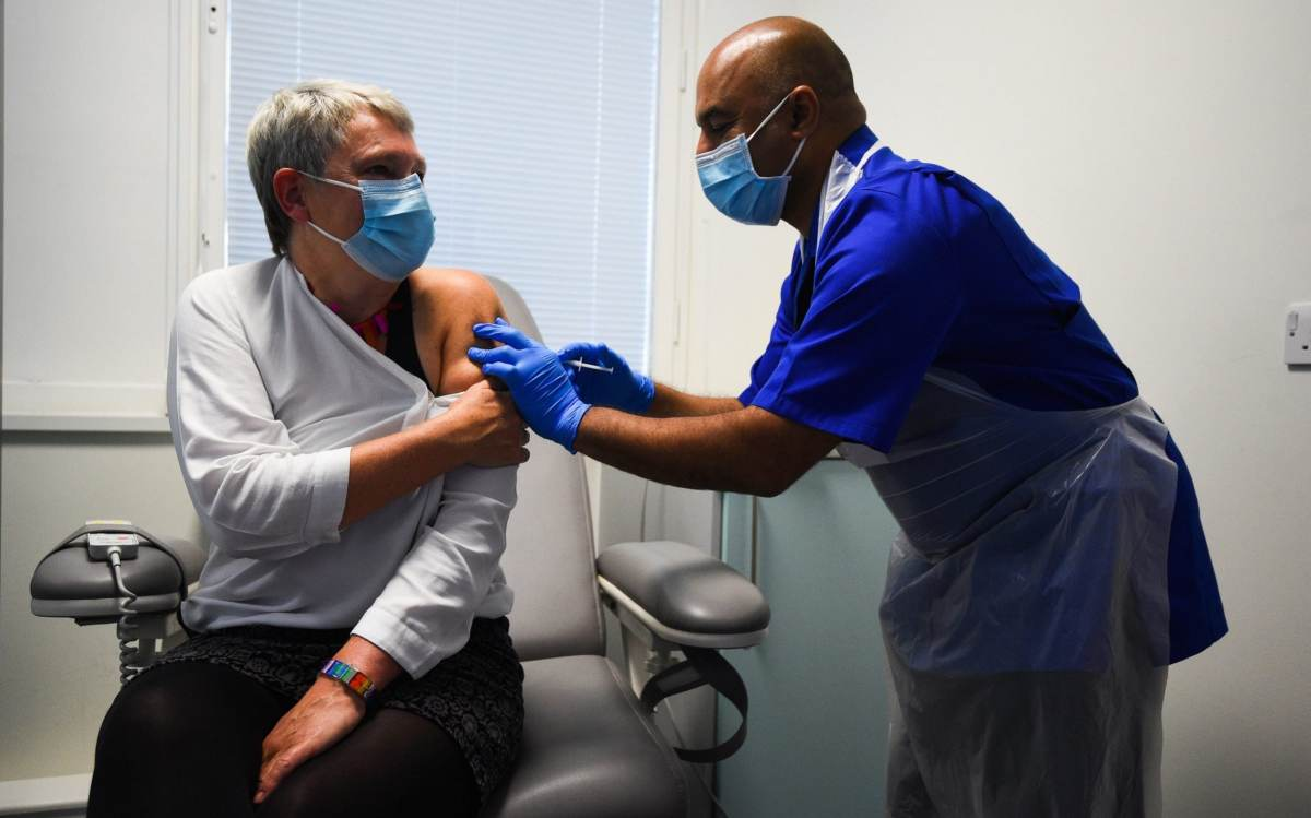 Lead research nurse Vash Deelchand gives a demonstration of the vaccine trial process as Kate Bingham, Chair of the Government's Vaccine Taskforce, starts her Novavax trial at the Royal Free Hospital, north London