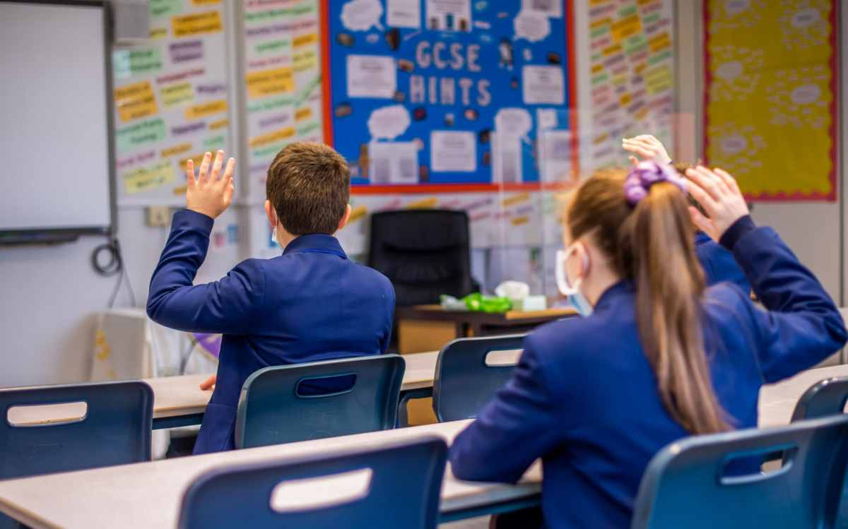 A pupil wearing a face mask raises his hand in class