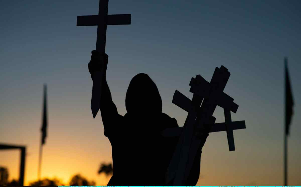 A Protester with crosses during demonstration in honor of victims of coronavirus in Brasilia