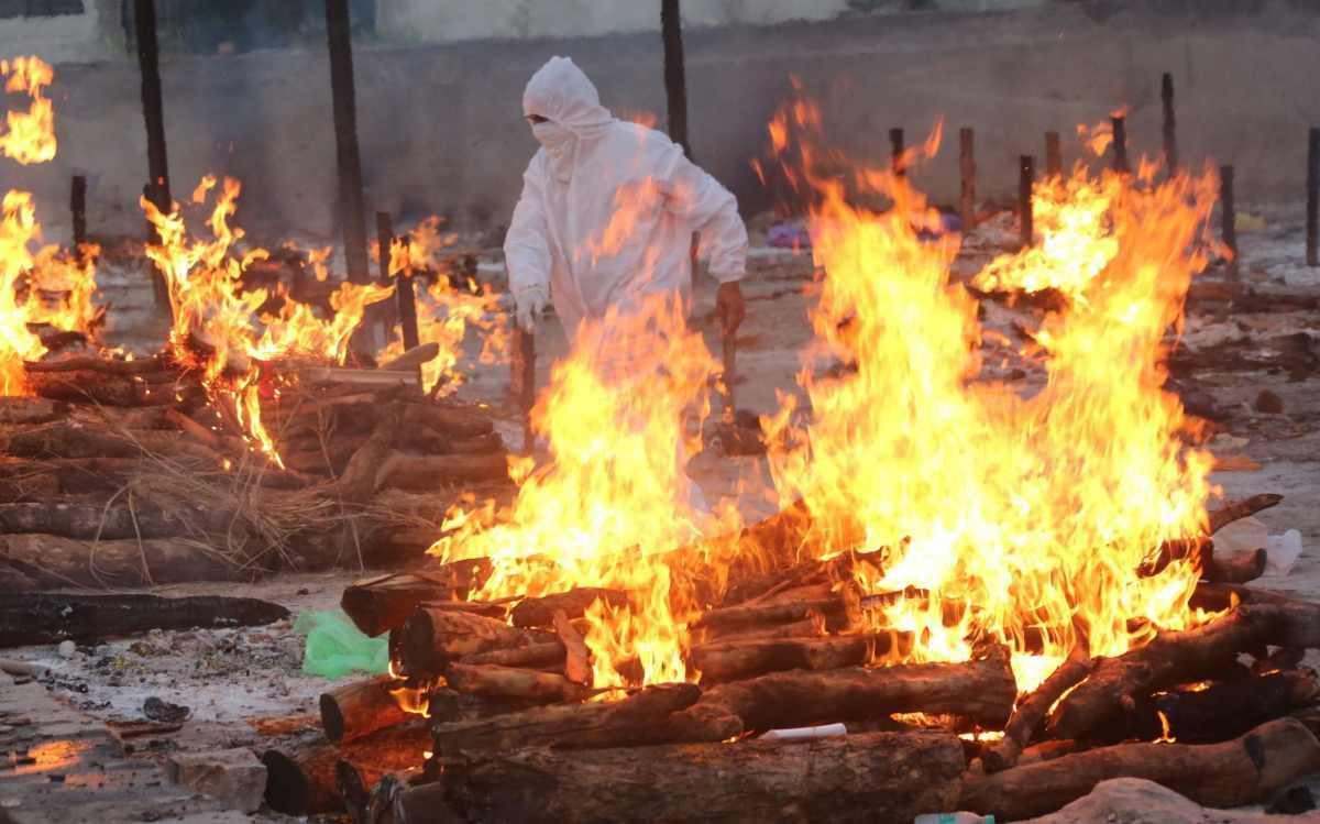 A social worker wearing PPE walks amid burning funeral pyres as he performs last rites of the Covid-19 victims in Bhopal