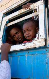 Refugees on a bus waiting to be taken to a temporary shelter, near the Sudan-Ethiopia border