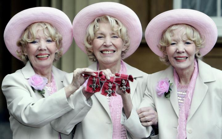 Babs, Joy and Teddie Beverley holding their MBEs at Buckingham Palace in London