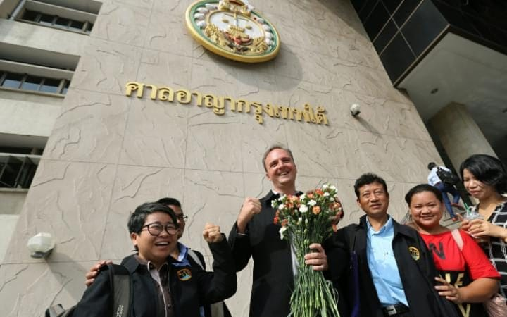 British lawyer and migrant workers' rights activist, Andy Hall (C) poses for a photo with supporters as he arrives for his trial at the Bangkok South Criminal Court in Bangkok, Thailand.