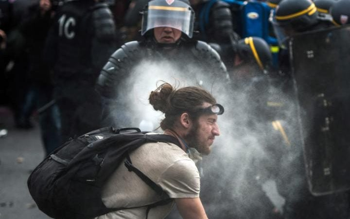 French riot police use tear gas against a demonstrator during a protest against the government's labour market reforms, at Place de la Nation