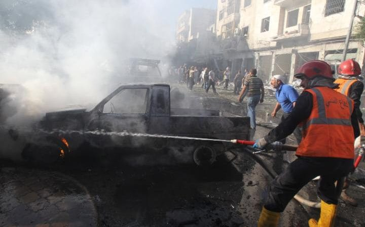 Civil defence members try to put out a fire after air strikes in Idlib, Syria