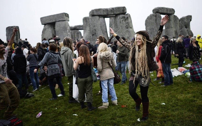 Revellers enjoying the summer solstice at a cloudy Stonehenge.