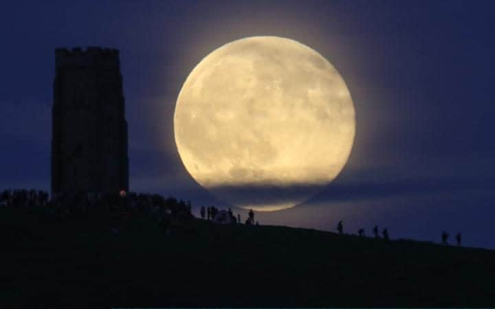 The so-called 'Strawberry Moon' rises behind Glastonbury Tor on in June 2016.
