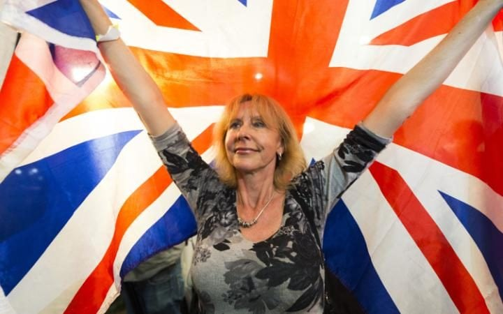 A Leave EU supporter hold a Union Jack flag aloft