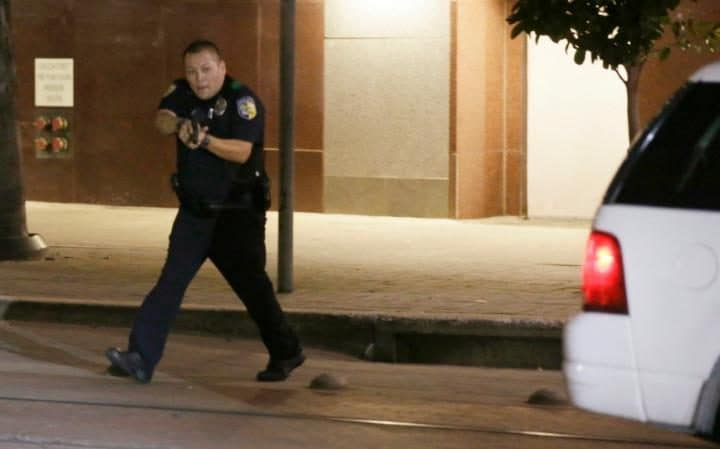 Dallas police move to detains a driver after several police officers were shot in downtown Dallas
