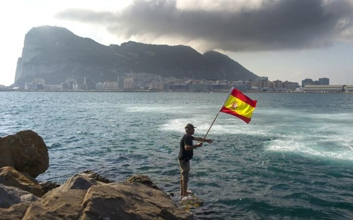 A fisherman holds a Spanish flag during a protest in the bay of Algeciras, near the Rock of Gibraltar