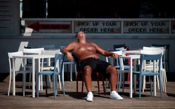 A man sunbathes on the boardwalk at Coney Island Beach, August 12, 2016 in New York City. Heat index temperatures of over 105 degrees
