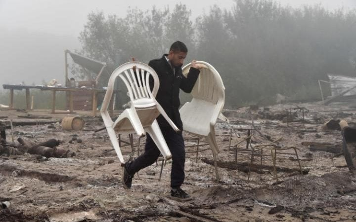 A man salvages some chairs from the ashes