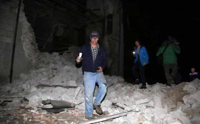 Residents walk past rubble in the village of Visso, central Italy, Wednesday, Oct. 26, 2016 following an earthquake