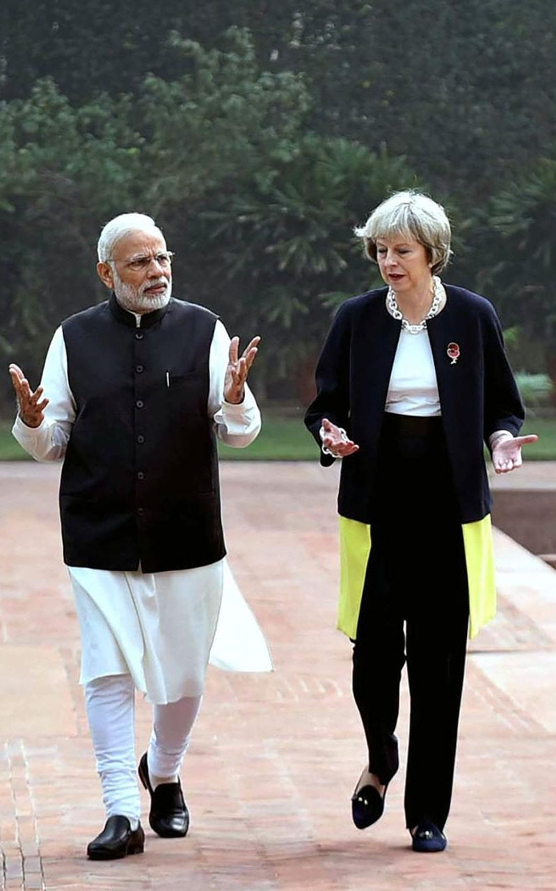 Indian Prime Minister Narendra Modi walks with Theresa May at Hyderabad House in New Delhi