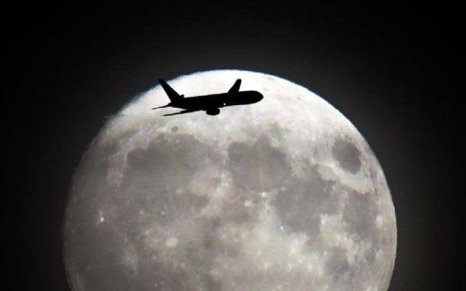 A commerical jet flies in front of the moon on its approach to Heathrow airport in west London