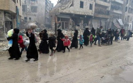 A line of refugees, mostly women in Islamic garb, accompanied by young children in winter coats, walk along a wet and muddy road alongside bombed out buildings