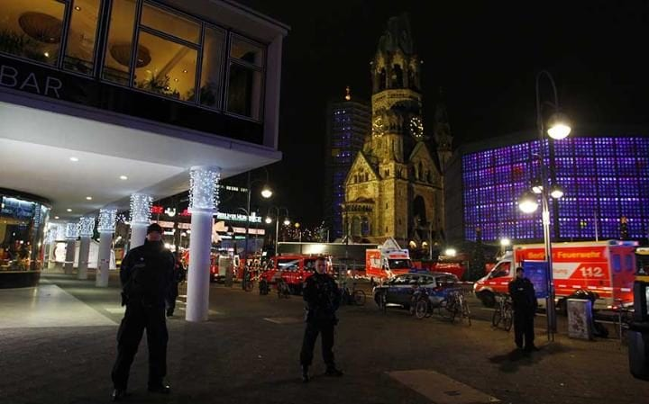 Security and rescue workers tend to the area after a lorry truck was ploughed through a Christmas market in Berlin