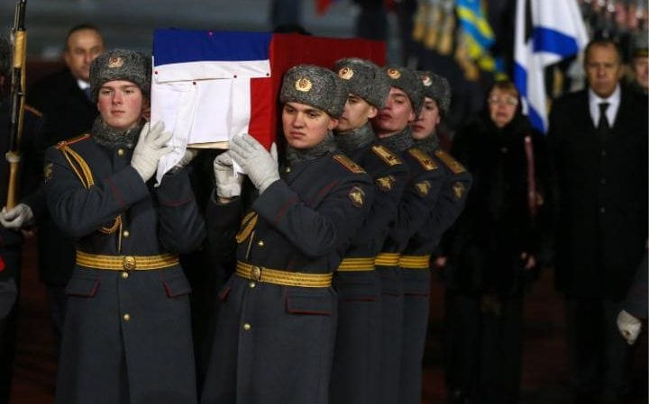 An honour guard carry Andrey Karlov's flag-draped coffin as it arrives in Moscow on Tuesday night