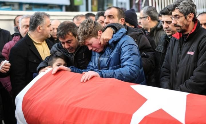 Relatives and friends mourn at a coffin during the funeral of Ayhan Arik, one of the 39 victims of the gun attack on the Reina