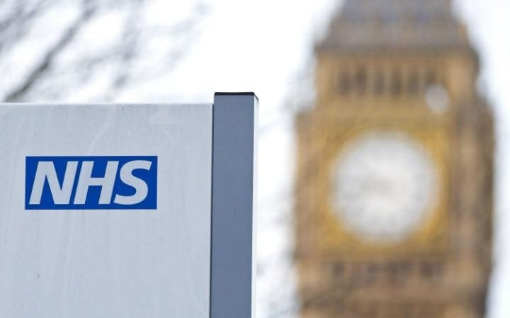 An NHS sign is pictured at St Thomas' Hospital in front of the Big Ben clock face
