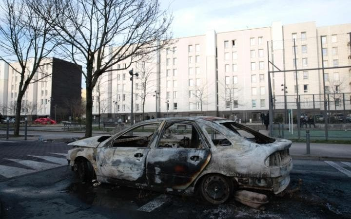 A picture taken on February 7, 2017 shows the wreckage of a burnt car in one of the main streets of the Cite des 3000 in Aulnay-sous-Bois
