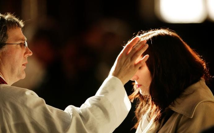 A churchgoer receives a cross of ashes painted on her forehead from a priest during Ash Wednesday Mass at Westminster Cathedral.