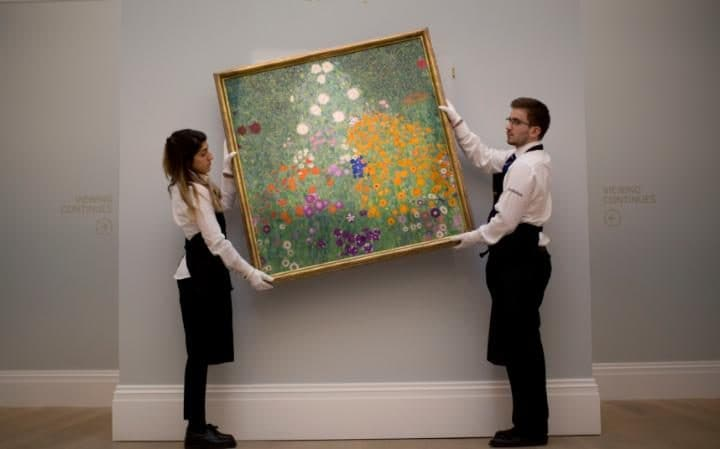 "Sotheby's auction house staff pose for photographers with Austrian artist Gustav Klimt's ""Bauerngarten (Blumengarten)"""