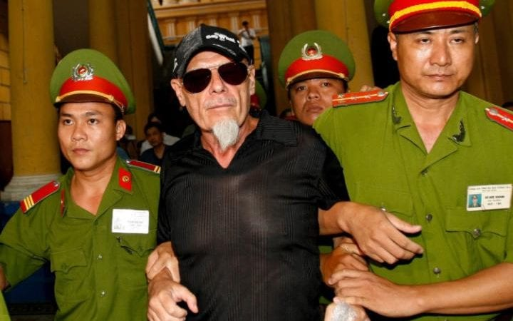 Fallen British glam rock star Gary Glitter (C) is escorted by police out of a courtroom after losing his appeal hearing in a child molestation case in Ho Chi Minh City, Vietnam