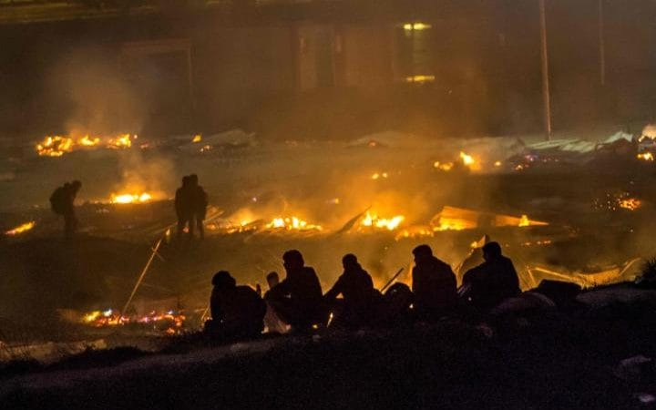 Migrants evacuate as a huge fire blazes through the Grande Synthe camp