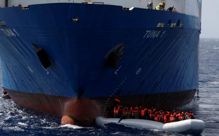 Migrants in a rubber dinghy hang on to ropes beneath the bow of the Panama-registered ship Tuna 1, after some migrants on another rubber dinghy drowned in the central Mediterranean in international waters off the coast of Libya