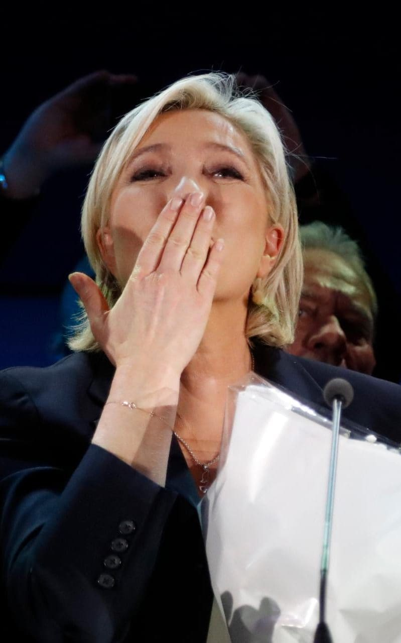 Far-right leader and candidate for the 2017 French presidential election, Marine Le Pen, blows a kiss while holding a bunch of flowers after exit poll results of the first round of the presidential election were announced at her election day headquarters in Henin-Beaumont