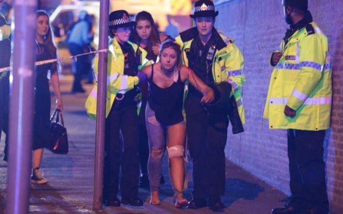 An injured woman is helped by police after the blast