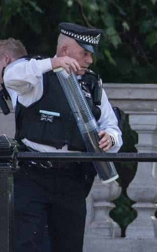 A police officer holds what is believed to be a large knife that is thought to have been seized from the man outside Buckingham Palace