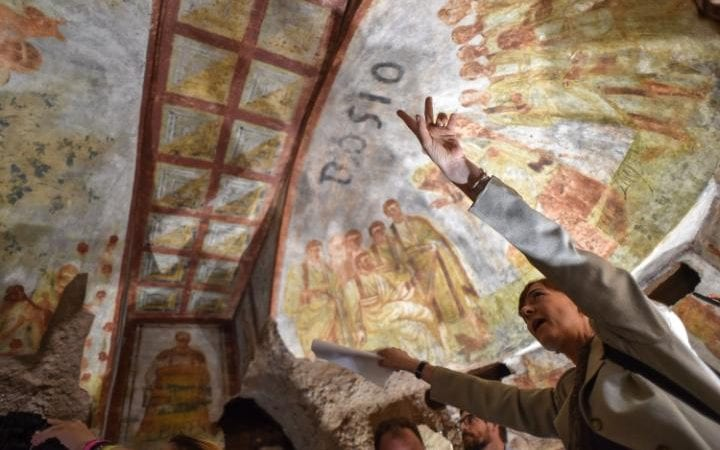 An expert points out newly-restored frescoes on the ceiling of a crypt deep underground in the Catacombs of St Domitilla in Rome.