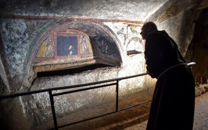 A monk gazes at a frescoed alcove in the Catacombs of St Domitilla in Rome.