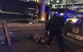 A suspect with what appears to be canisters strapped to his body, lies on the ground in Borough Market