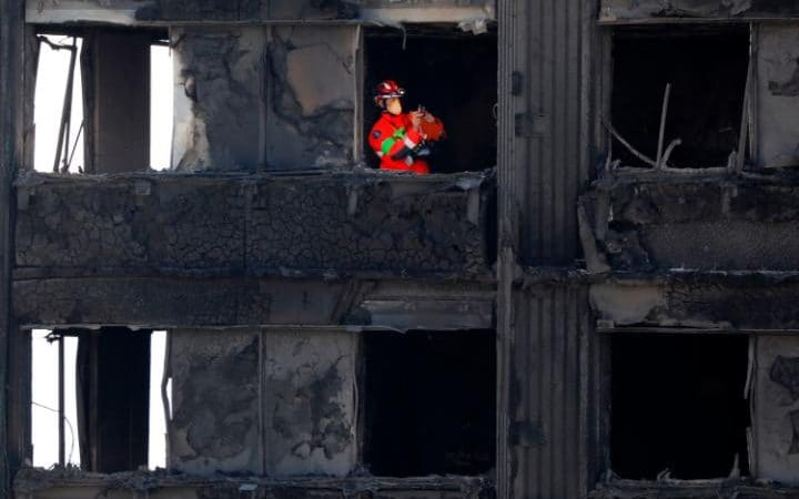 Members of the emergency services work inside the charred remnains of Grenfell Tower