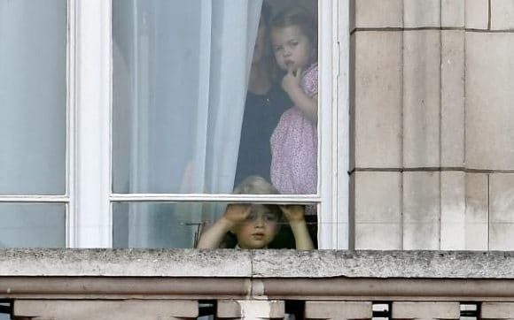 Prince George and Princess Charlotte of Cambridge watch through the window of Buckingham Palace as they attend Trooping the Colour at Buckingham Palace