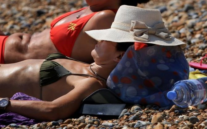 A lady sunbathes as they enjoy the hot weather on the beach in Brighton, East Sussex